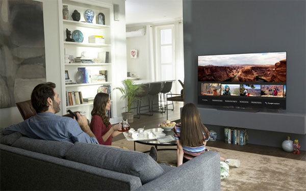 Familie sitzt im Wohnzimmer vor dem Fernseher