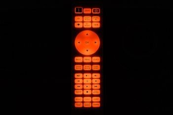 Fernbedienung im Dunkeln mit orange leuchtenden Tasten